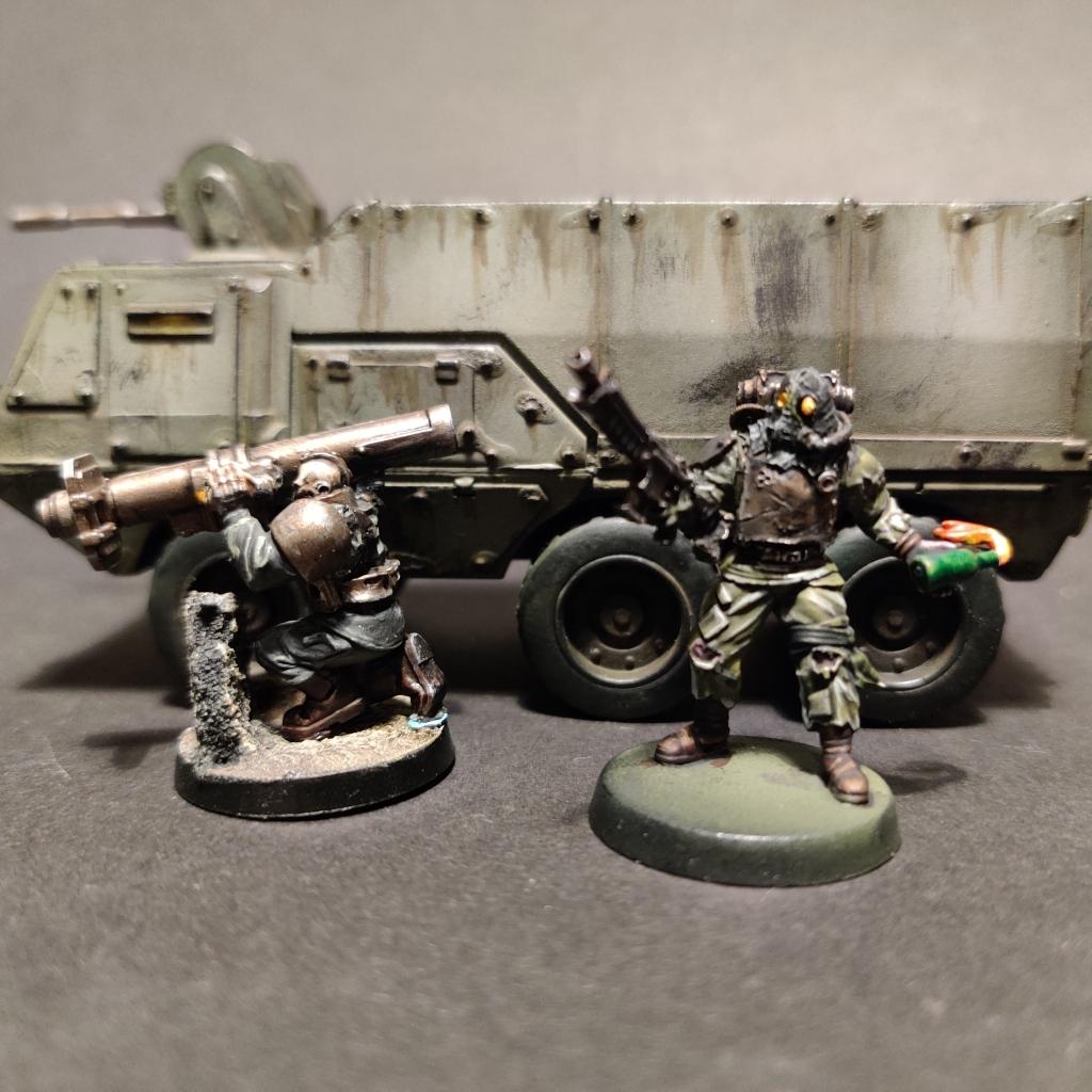 Two warhammer 40k renegade guardsmen in front of a troop truck